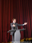 Picture of a businessman or maybe a politician on a stage with a podium or lectern giving a speech to an audience. The man is gesturing with his arms held out in front of him, palms up.  The man is smiling.